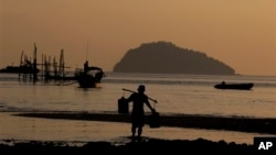 A fisherman carries fresh water to his fishing boat on Nyuang Wee Islandin Mergui Archipelago, Burma. The archipelago is thought by scientists to harbor some of the world's most important marine biodiversity.