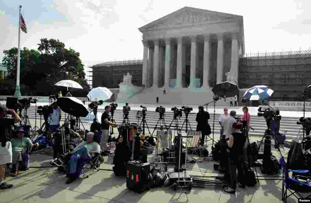 Members of the media gather for a stakeout in front of U.S. Supreme Court in Washington.