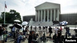 Members of the media gather for a stakeout in front of U.S. Supreme Court in Washington, June 25, 2012.