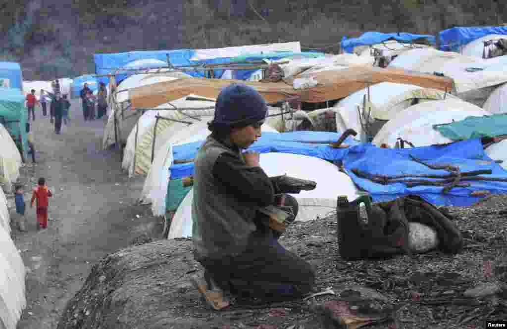 시리아와 터키 국경 지역의 난민 대피소에서 10일 한 소년이 나무를 옮기고 있다.