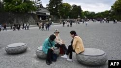 Para pengunjung berbincang di halaman Istana Kekaisaran di Tokyo, 29 April 2019, sehari sebelum upacara turun takhta Kaisar Jepang Akihito.