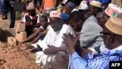 Des hommes prient près d'une tombe dans un cimetière de la capitale régionale Ziguinchor, au sud du Sénégal, le 7 janvier 2018.