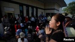 安保人员逮捕数名向大使馆提交请愿书的抗议者后,另一名抗议者在美国大使馆前哭泣。(缅甸,金边,1月21日,2014)
