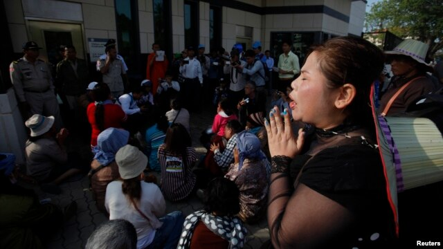 A protester cries in front of the U.S embassy after others were detained by security guards during an attempt to deliver a petition to the embassy in Phnom Penh, Cambodia, Jan. 21, 2014.