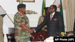 로버트 무가베 짐바브웨 대통령(오른쪽)이 지난 19일 의회에서 가진 생방송 TV연설에 앞서 짐바브웨 군 수장인 콘스탄티노 치웬가 사령관과 만나 악수하고 있다.