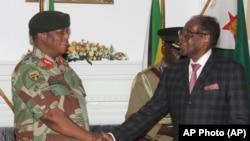 Le président zimbabwéen Robert Mugabe, à droite, serre la main au général de l'armée Constantino Chiwenga avant de prononcer son discours lors d'une émission en direct à State House à Harare, 19 novembre 2017.