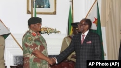 FILE: Zimbabwean President Robert Mugabe, right, shakes hands with Army General Constantino Chiwenga before delivering his speech during a live broadcast at State House in Harare, Sunday, Nov, 19, 2017.
