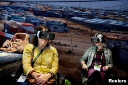 """FILE - Participants watch virtual reality movie """"Born into Exile"""", about two pregnant women who are due to deliver in Za'atari refugee camp, Jordan, during Women Deliver, a major women's health and rights conference in Copenhagen, Denmark, May 17, 2016."""