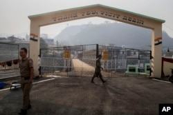 An Indian army soldier, center, and a Mizo policeman patrol at the India-Myanmar border gate , in Chaamphai village, in Mizoram, India, Saturday, March 20, 2021.