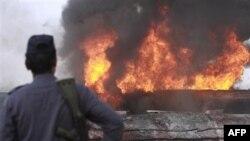 Pakistanski policajac posmatra jedan od zapaljenih kamiona-cisterni