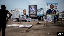 Seorang pria mengamati poster kampanye di distrik Lingwala, Kinshasa, 18 Desember 2018 (foto: John Wessels/AFP)