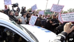 Palestinian protesters surround a vehicle in the convoy of U.N. Secretary-General Ban Ki-moon as it arrives at Erez border crossing between Israel and Gaza, February 2, 2012.