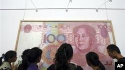 参观者在成都的展览会上观看关于人民币百元钞票的美术作品(2011年10月)