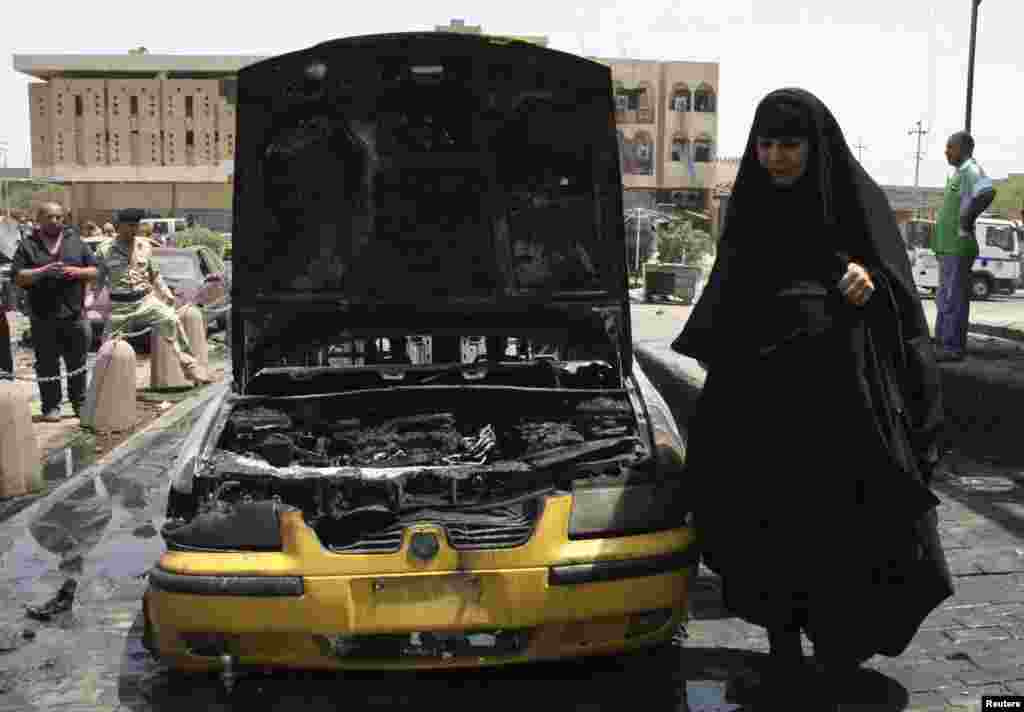 A woman walks at the site of car bomb attack in Sadr city, northeastern Baghdad, Iraq, July 23, 2012.