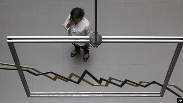 An employee of the Athens Stock Exchange speaks on her cell phone in Athens, August 8, 2011.