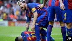 Lionel Messi s'incline pour assister son coéquipier Neymar du FC Barcelone, touché par un projectile lancé par un spectateur lors du match de la Liga espagnole entre Valence et le FC Barcelone au stade Mestalla à Valence, Espagne, le 22 octobre 2016.