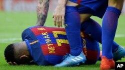 Neymar du FC Barcelone, touché par un projectile, se tord des douleurs sur la pelouse, lors du match de la Liga espagnole de football entre Valence et le FC Barcelone au stade Mestalla à Valence, en Espagne, 22 octobre 2016.