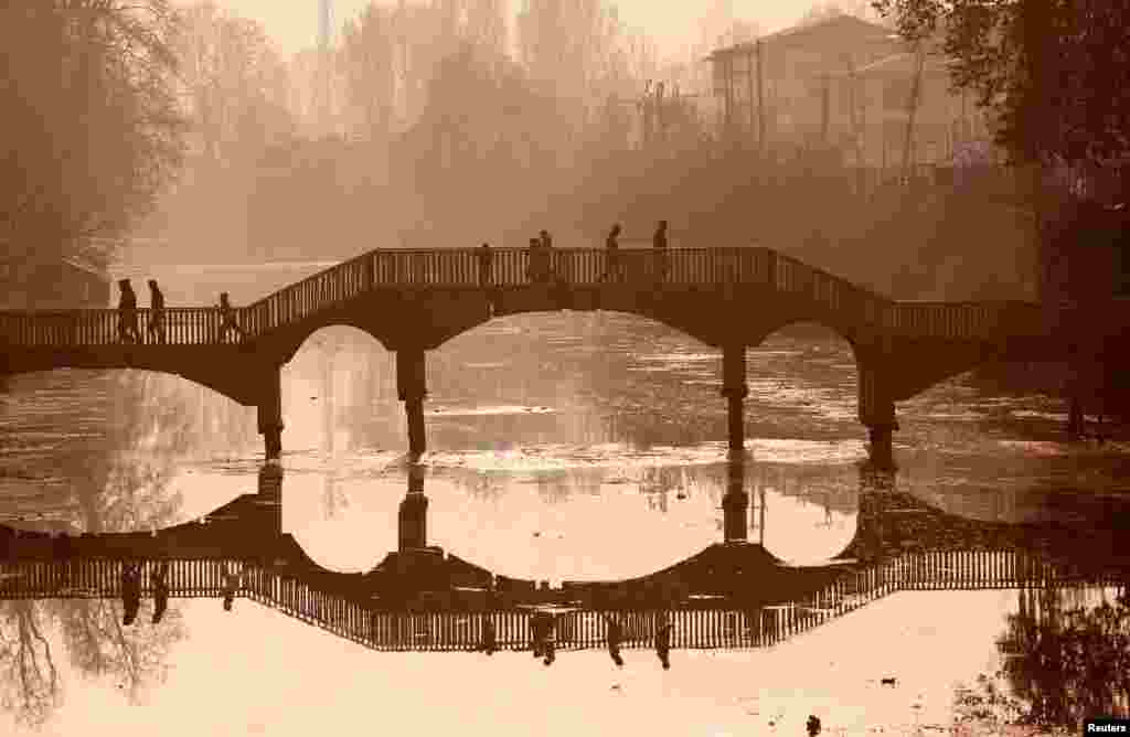 People walk on a wooden footbridge across a canal during an autumn day in Srinagar, India.