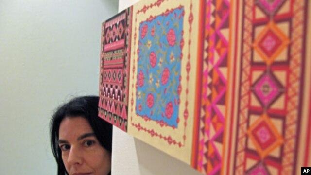 Artist Helen Zughaib takes a peek around her piece 'Another Wall,' June 2011