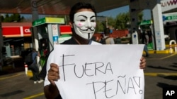 "A masked protester holds a sign that says ""Pena Out!"" as people angry over hiked gas prices under President Enrique Pena Nieto's government block for hours one of the city's oldest gas stations at a main intersection in Mexico City, Jan. 2, 2017."