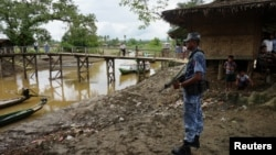 FILE - A Myanmar border guard police officer stands guard in Taung Bazar village, Buthidaung township, northern Rakhine state, Myanmar, July 13, 2017.