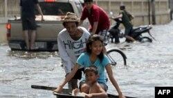 Dân chúng di chuyển trong làn nước lụt trong thủ đô Bangkok hôm 21/10/11