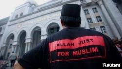 Một người đàn ông Hồi giáo mặc áo in hàng chữ 'Allah chỉ được dùng bởi người Hồi giáo' đứng bên ngoài tòa án ở Putrajaya, ngày 23/6/2014.