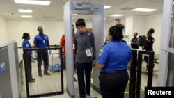 FILE - Autistic boy Jeffery Jr. Simonton (C) walks through the metal detector while a Transportation Security Administration (TSA) agent looks on.