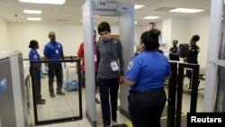 Petugas keamanan bandara AS mengamati seorang penumpang melewati alat pemindai (foto: dok).