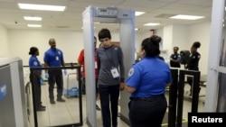 Hành khách đi ngang qua máy dò kim loại trong khi nhân viên Cơ quan Quản lý An ninh Vận tải theo dõi kết quả, Los Angeles, California