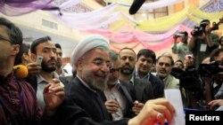 Hassan Rohani, déposant son bulletin de vote dans l'urne à Téhéran lors de l'élection présidentielle du 14 juin 2013.