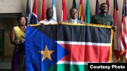 From left, Regina Onyeibe, Africa liaison for Dallas, Dallas-area resident Michael Majok, Dallas City Councilman Dwaine Caraway and pro basketball star Luol Deng participate in the raising of the South Sudanese flag at City Hall in Dallas, Texas, July 2017.