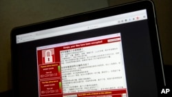 A screenshot of the warning screen from a purported ransomware attack, as captured by a computer user in Taiwan, is seen on laptop in Beijing, May 13, 2017. Dozens of countries were hit with a huge cyberextortion attack Friday that locked up computers and