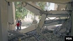 Dua anak Libya bermain di reruntuhan gedung, yang menurut Tripoli adalah sebuah gedung sekolah yang hancur akibat serangan NATO (4/8).