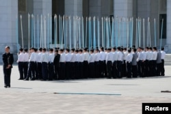Students hold flag poles as they practice for an apparent parade to celebrate the Workers' Party of Korea (WPK) congress in central Pyongyang, North Korea, May 7, 2016.