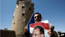 ຜູ້ສະໜັບສະໜູນຄົນນຶ່ງ ຂອງອະດີດປະທານາທິບໍດີ Ali Abdullah Saleh ທີ່ຖືກຂັບໄລ່ອອກຈາກຕຳແໜ່ງ ຖືຮູບພາບຂອງທ່ານ.