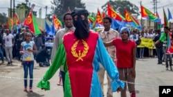 Một người phụ nữ mặc quần áo mang màu sắc của lá cờ Eritrea với hai sợi xích tượng trưng tại một cuộc biểu tình của những người tị nạn Eritrea và bất đồng chính kiến bên ngoài trụ sở Liên minh châu Phi tại Addis Ababa, Ethiopia, ngày 23 tháng 6 năm 2016.