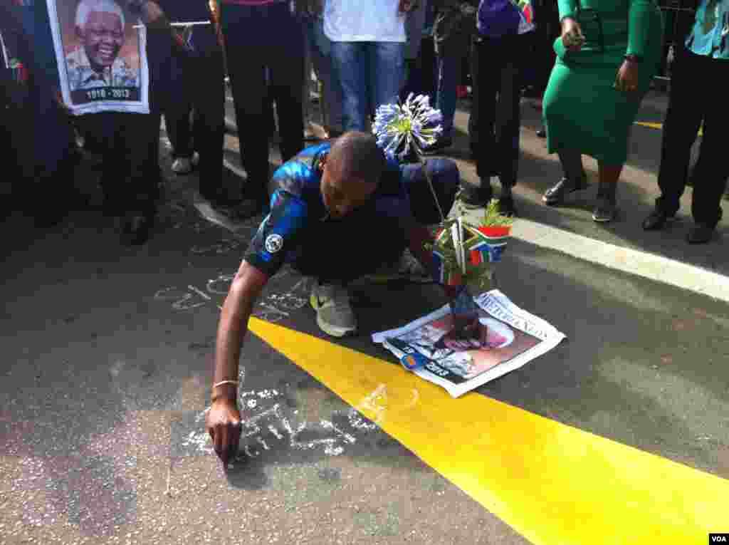 Un chico escribe un saludo a Mandela sobre el pavimento de la calle. [Foto: Celia Mendoza, VOA].