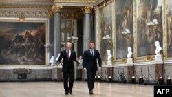 ប្រធានាធិបតីរុស្ស៊ី Vladimir Putin (ឆ្វេង) កំពុងធ្វើដំណើរជាមួយប្រធានាធិបតីបារាំង Emmanuel Macron ដើម្បីចូលរួមក្នុងសន្និសីទសារព័ត៌មាននៅរាជវាំង Versailles នៅជិតទីក្រុងប៉ារីស។