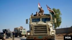 Les troupes irakiennes avancent dans Mossoul portant sur leurs véhicules des bannières chiites en plus du drapeau national irakien, 3 novembre 2016. (VOA/ Jamie Dettmer)
