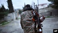 Một chiến binh sắc tộc Armenia mang súng máy Kalashnikov cho đồng đội ở Martakert, khu vực ly khai Nagorno-Karabakh, Azerbaijan, thứ Hai ngày 4 tháng 4 năm 2016.