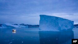In this Aug. 15, 2019, file photo, a boat navigates at night next to large icebergs in eastern Greenland. (AP Photo/Felipe Dana, File)
