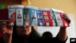 Un assesseur exhibe un bulletin de vote au nom du président Evo Morales après la fermeture des bureaux de vote à La Paz, en Bolivie, le dimanche 20 octobre 2019. (AP Photo / Juan Karita)