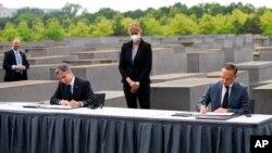 Američki državni sekretar Antony Blinken (L) i njemački ministar inostranih poslova Hajko Mas potpisuju sporazum o pokretanju Dijaloga SAD i Nejmačke o holokaustu, pored spomenika žrtvama holokausta u Berlinu (Foto: AP/Markus Schreiber)