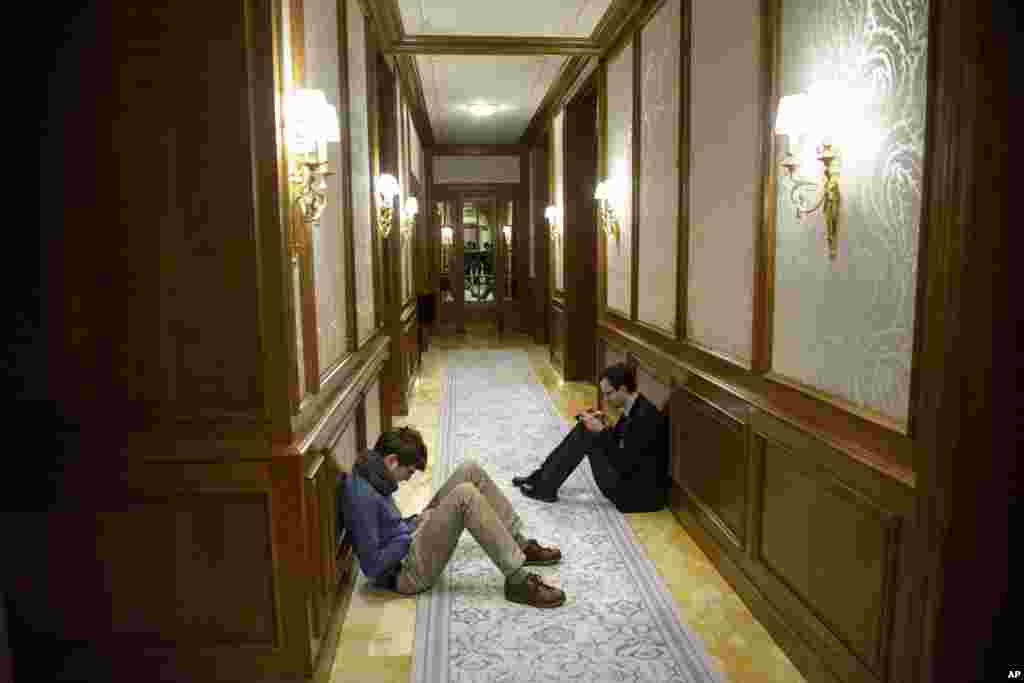 Reporters sit in a hallway during the Iran nuclear program negotiations at the Beau Rivage Palace Hotel in Lausanne, Switzerland, April 1, 2015.