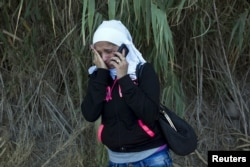 FILE - A Syrian refugee burst into tears while contacting her father in Syria to inform him that she arrived safely on a dinghy on the Greek island of Lesbos, Sept. 11, 2015.