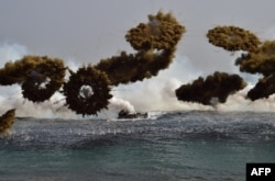 FILE - South Korean Marine amphibious assault vehicles fire smoke shells to land on the seashore during a joint landing operation by US and South Korean Marines in the southeastern port of Pohang, March 30, 2015.