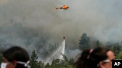 Firefighters drop water on a forest fire in Portezuelo, Chile, Jan. 29, 2017.