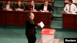 FILE - Tunisia's Speaker of the Assembly Mustapha Ben Jaafar casts his vote over the composition of an election commission that will oversee a vote later this year, Tunis, Jan. 8, 2014.