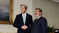 Menlu AS John Kerry (kiri) berjabat tangan dengan Presiden Mesir Mohamed Morsi di Istana Kepresidenan Mesir di Kairo (3/3).